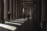 A woman walks down a covered walkway in Sydney