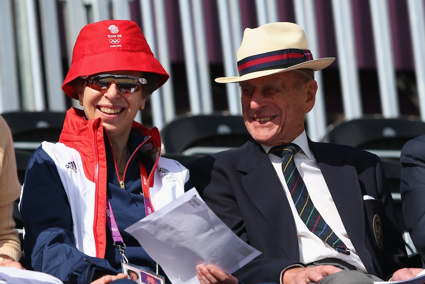 Princess Anne in sunglasses and a bucket hat sits next to her father Prince Philip.