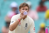Joe Root squats as he takes a drink from a water bottle