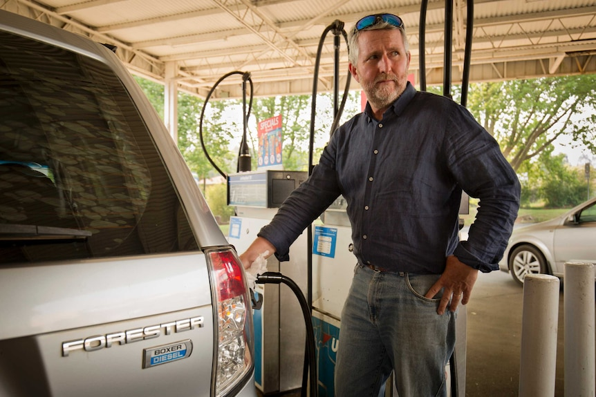 Peter Lynch stands at a fuel bowser filling up his Subaru Forester.