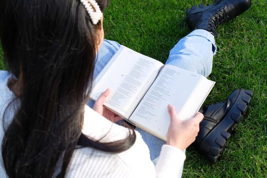 Overhead shot of Shu Xian Leong reading Bible on grass.