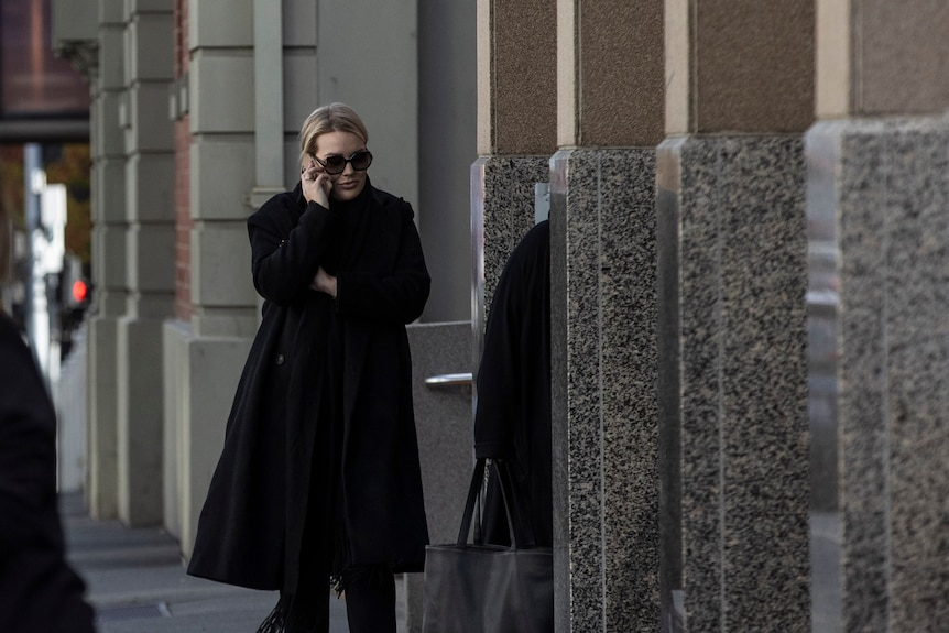 Woman in dark glasses and long black coat walks outside court while on mobile phone.