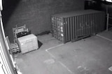 A black and white picture from CCTV footage showing a yard outside  abuilding with a man crawling on the ground near a wall.