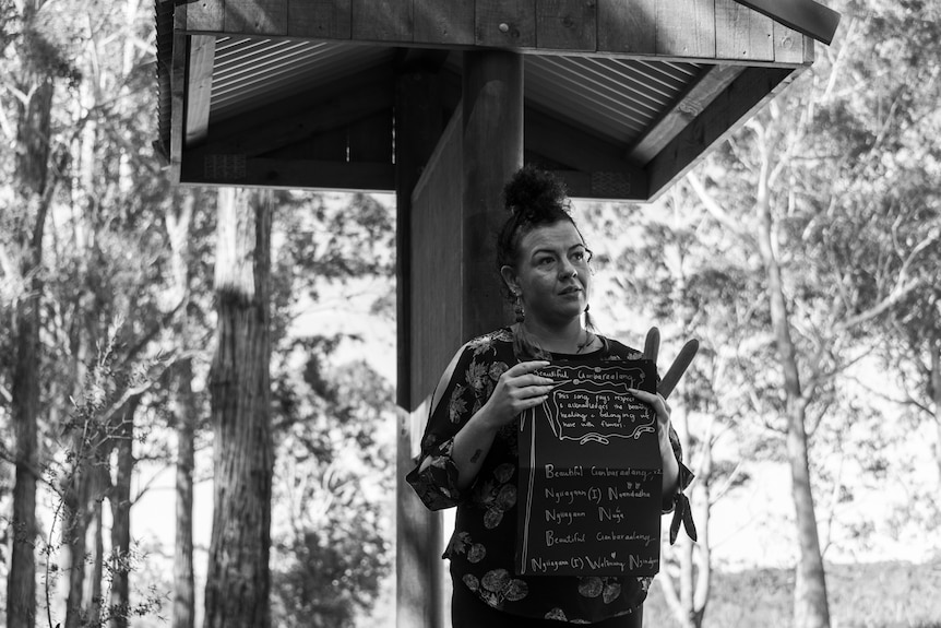 Woman holding clapsticks and an open book with song lyrics handwritten in Aboriginal language