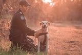 A man in police uniform is kneeling by his golden labrador