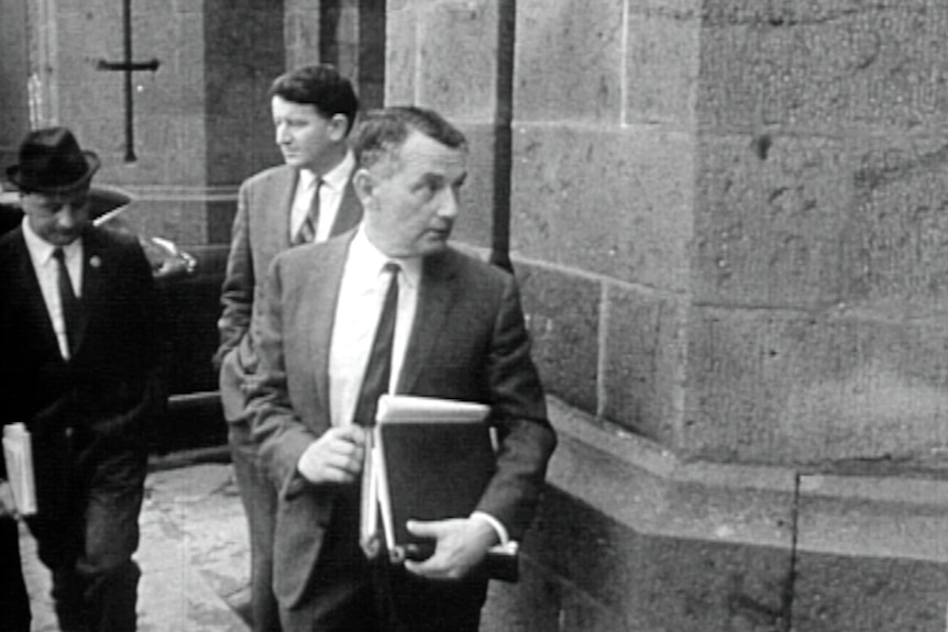 A black-and-white historical image of a lawyer carrying a stack of books walking into a stone courthouse