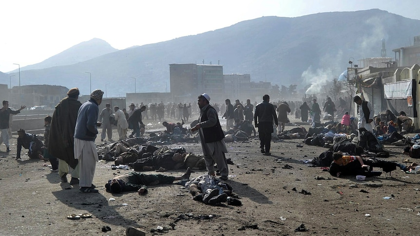 Afghans run from an explosion during a religious ceremony in Kabul city centre