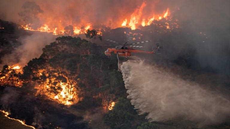 A helicopter travelling over burning bushland.