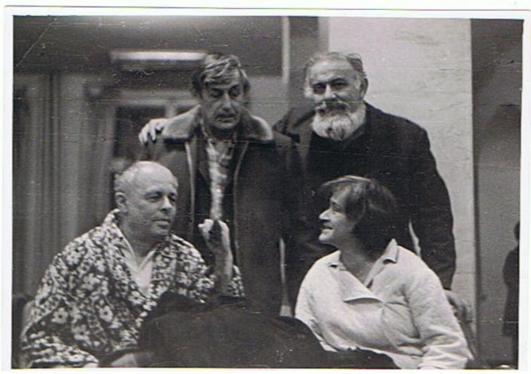 Black and white photograph of four people talking in a room.