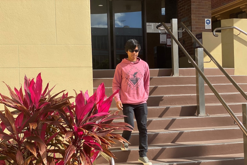 A man in sunglasses and a pink hoodie leaves court.