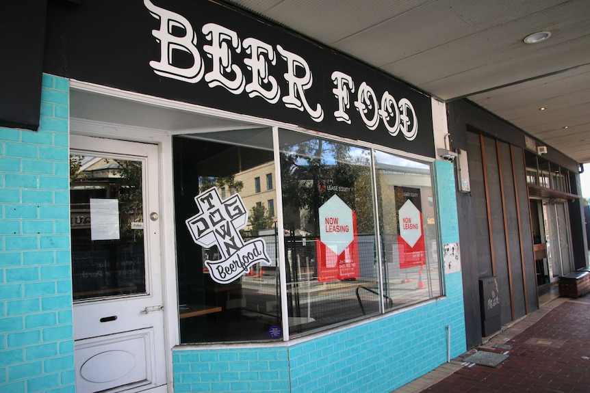 For lease signs in the windows of a bar and restaurant.