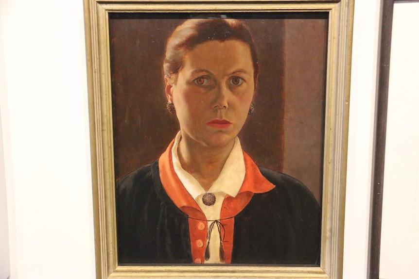A portrait of Stella Bowen hangs on a wall.