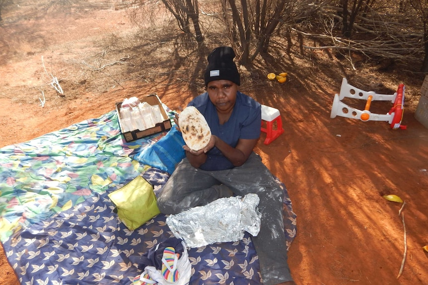 Verna Wilson sits on a picnic blanket and holds up some damper she made for her family.