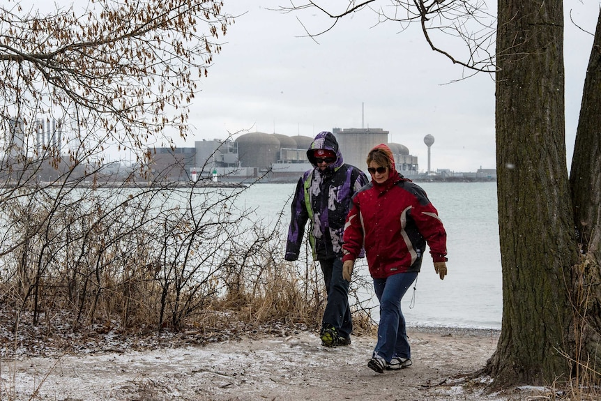 two people walk along snow covered ground in the foreground as a nuclear plant is seen across a body of water behind them
