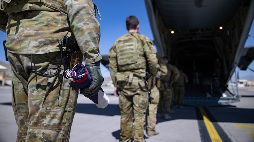 A soldier holds a rolled up Australian flag as he prepares to board a military aircraft.