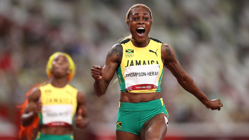 A Jamaican female sprinter celebrates after crossing the finish line to win gold at the Tokyo Olympics.