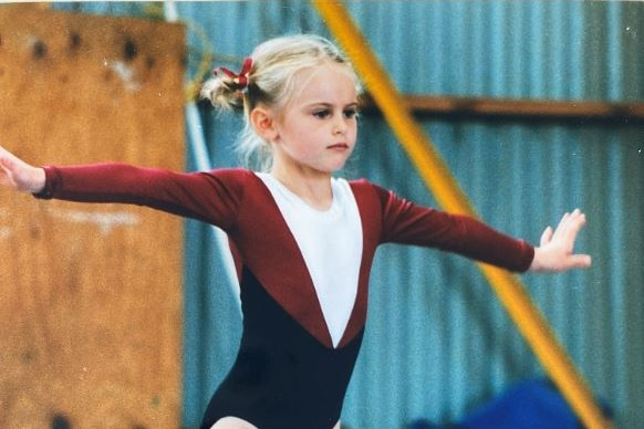A child with blond hair in pig-tails and wearing a marrone leotard balances, standing with arms outstretched, on a beam.