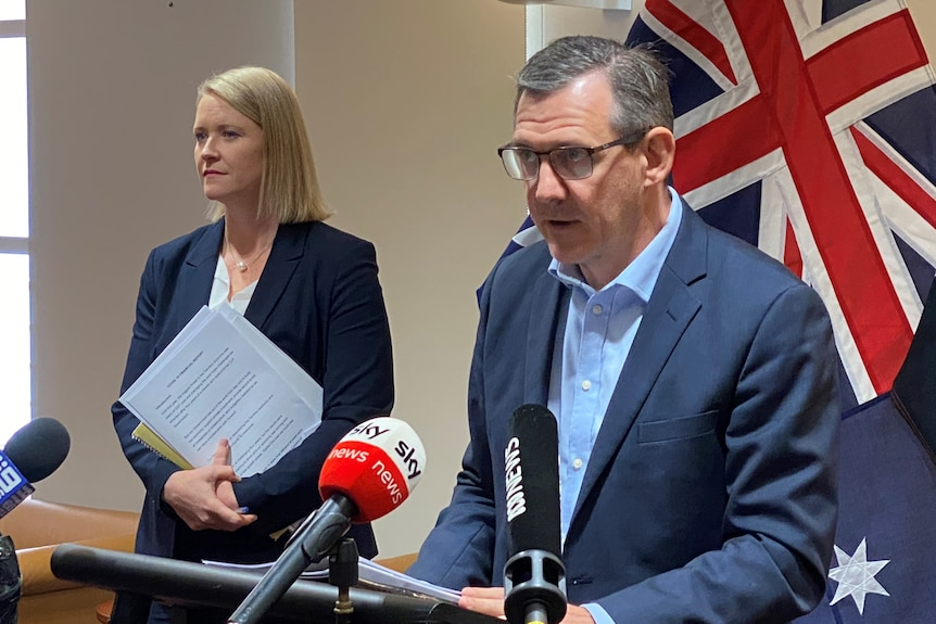 Chief Minister Michael Gunner and Treasurer Nicole Manion are at a press conference looking serious.