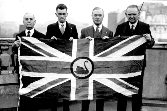 Black and white pic of four men holding the proposed new WA flag - a Union Jack with a black swan in the centre.