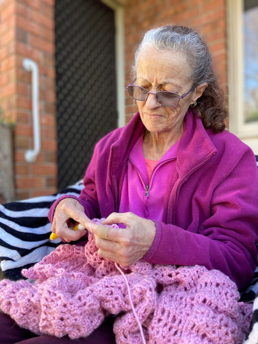 Wendy Morgan sits outside her apartment doing crochet.