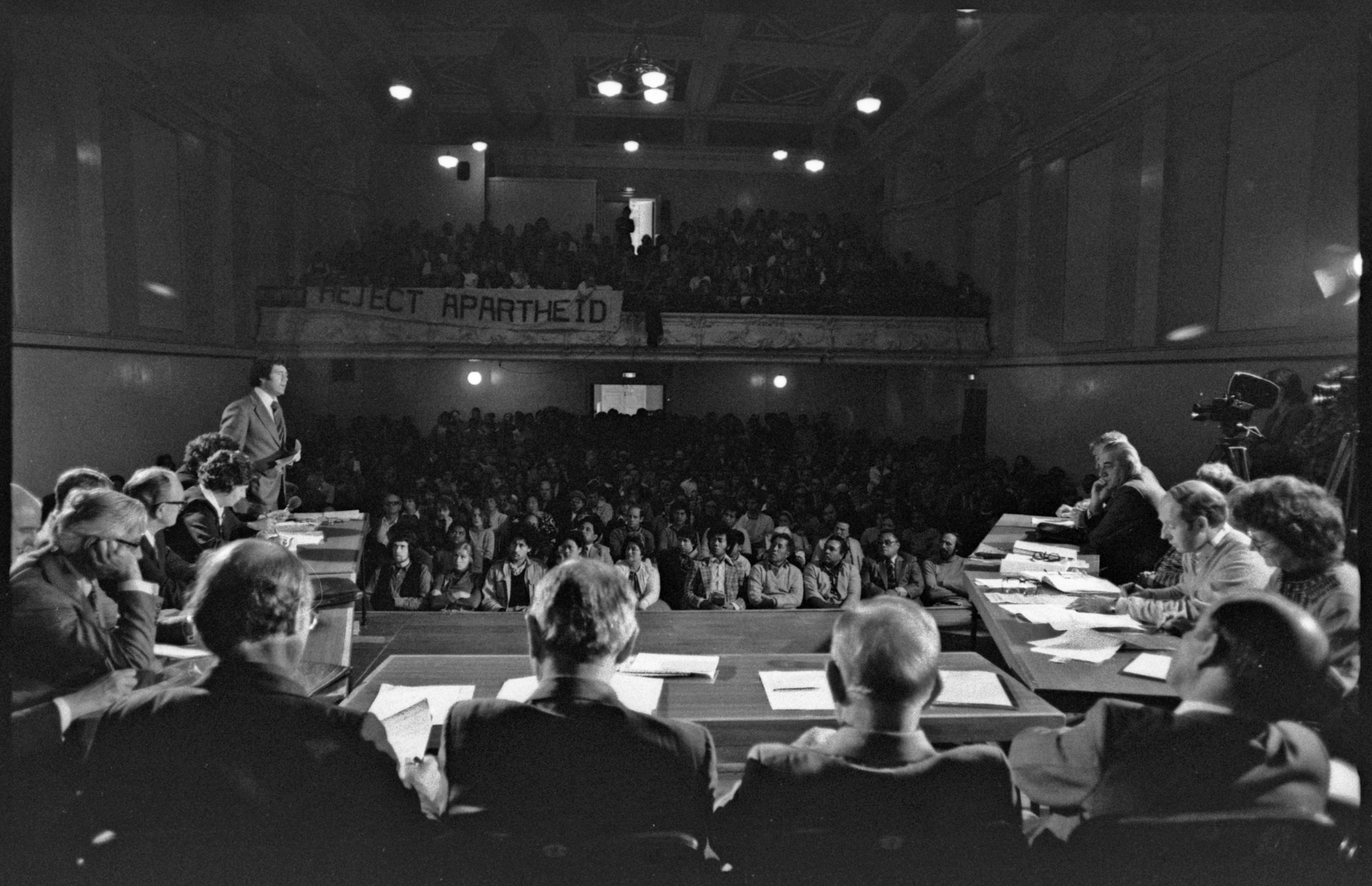 A black and white image shows a meeting on stage with a packed audience.