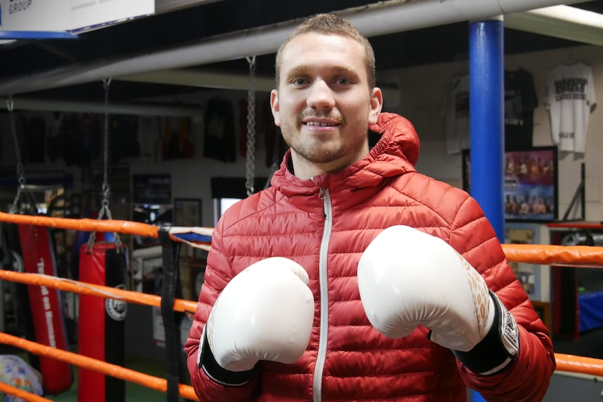 A man wearing a red puffer jacket, smiling at the camera with boxing gloves on.