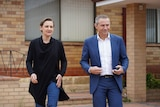 Amber-Jade and Roger walking out of a cream-brick suburban house.