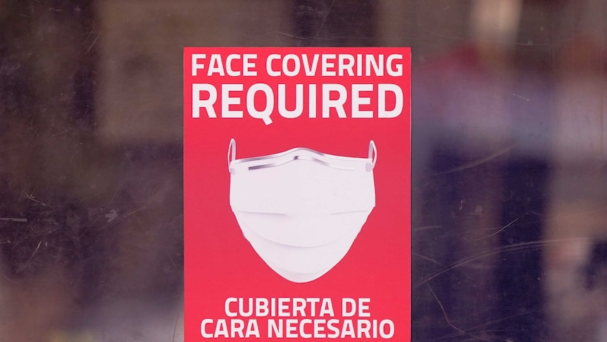 A mask required sign is displayed on the entrance to a business