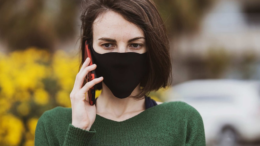 A woman wearing a black mask and green jumper on the phone in a story about what not to say to people in coronavirus lockdown.