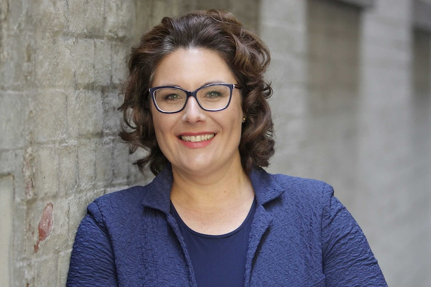 A woman with curly brown hair, glasses and blue jacket leans against a brick wall smiling widely.