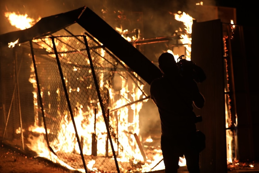 Cameraman films flames burning down building and wire fence.