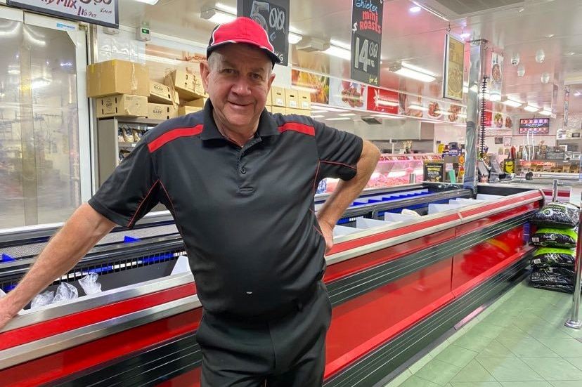 A man stands in a butcher deli and looks at the camera.