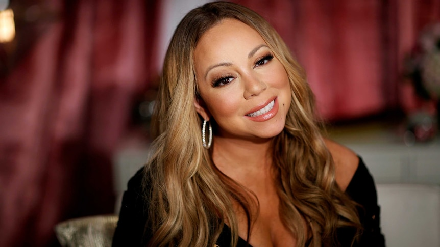 Mariah Carey smiles and tilts her head to the side as she poses for a portrait.