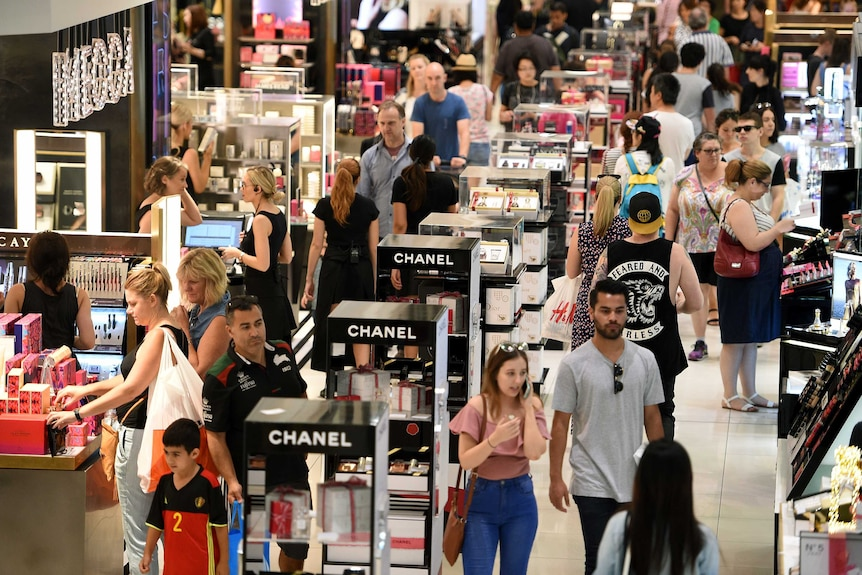 Shoppers mill around a cosmetics department in a large department store