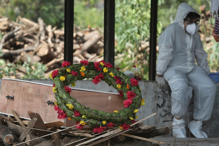 A wreath lies on the coffin of a COVID-19 victim next to a person wearing a PPE