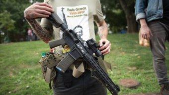 A man holding a gun with an Antifa shirt