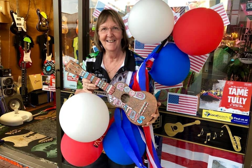 Business owner in shopfront with flag