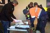 A worker in hi-vis clothing leans over a table signing a piece of paper as a man looks through a file folder opposite him.