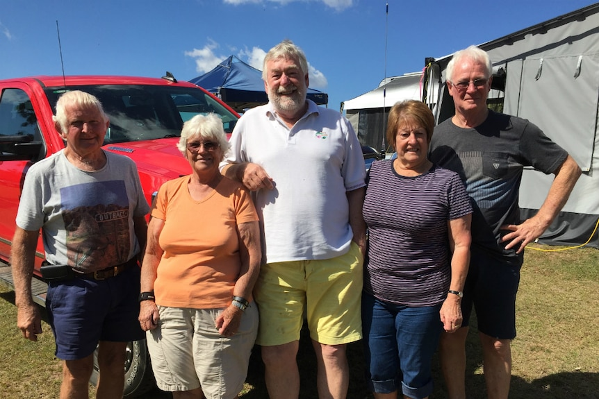 Three men and two women stand smiling at a campsite.