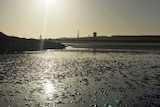 View at sunrise of the Burrup industrial area in the Pilbara, from Hearson Cove mud flats
