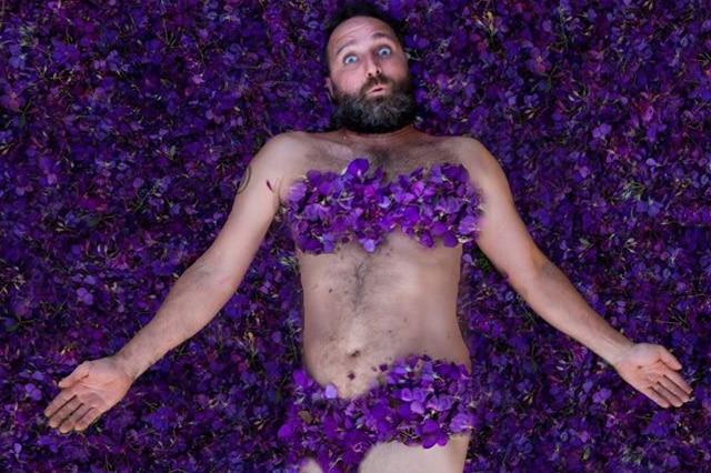 Scott Collins lying in a bed of petals.