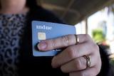 A hand holding an Indue cashless welfare card.