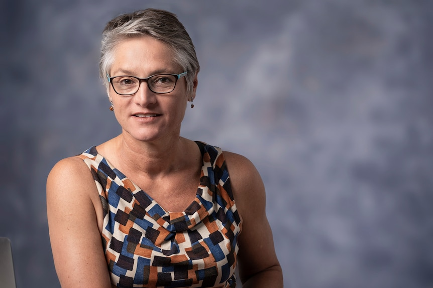 A portrait-style photo of a woman with short grey hair and glasses, against a grey backdrop.