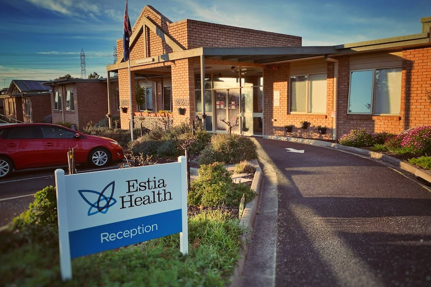 A sign reads 'Estia Health Reception' outside a one-storey brick building.