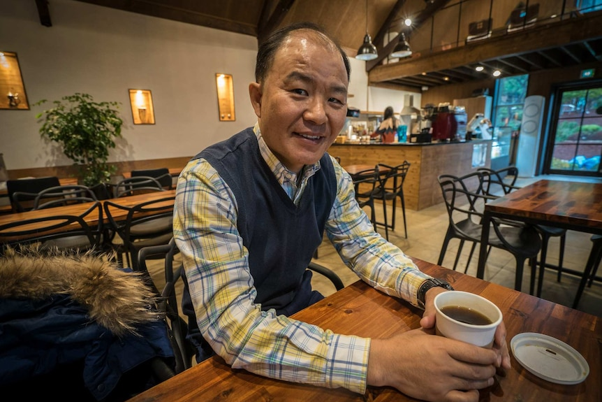 A middle-aged balding Asian man sits in a cafe nursing a black coffee in a paper cup with its lid laying upside down.