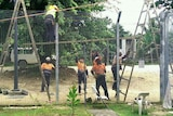 Workers in high-vis vests remove wires fences at Manus Island processing centre
