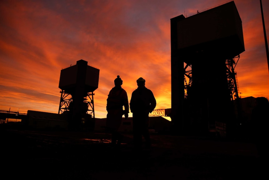 Two miners walking through a coal mine at sunset
