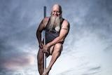 Man approaching 60, sporting bushy grey beard, balances on pole