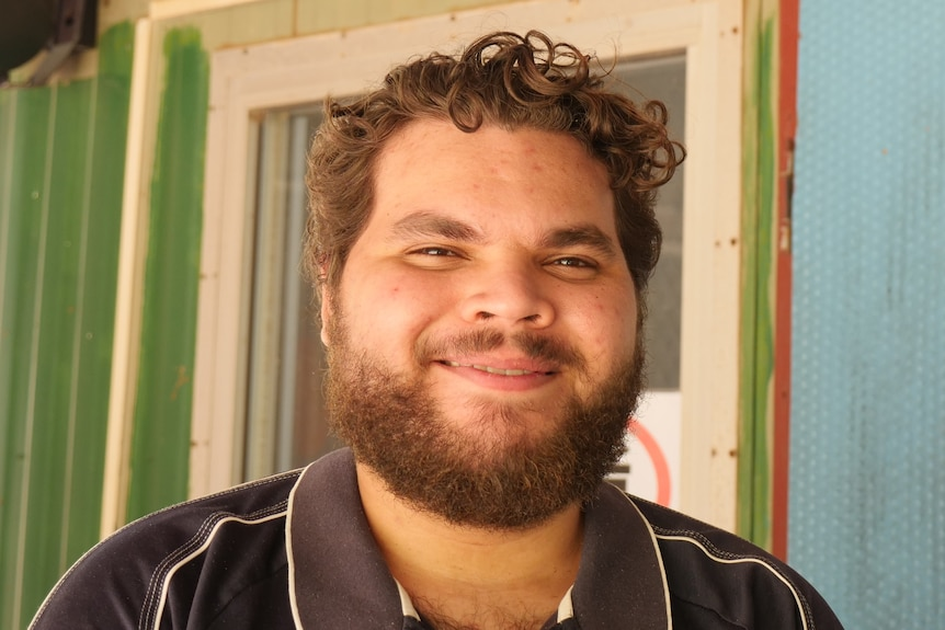 A young, dark-bearded Aboriginal man standing outside an outback radio studio