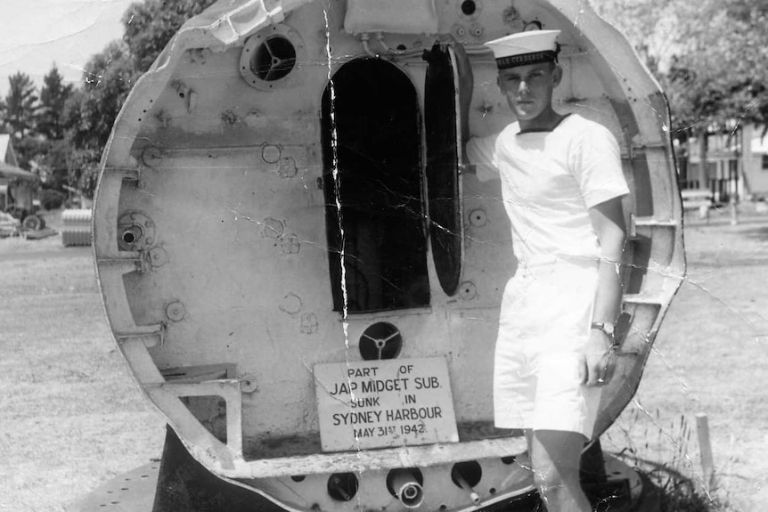Young sailor on left in front of the back of a Japanese midget submarine with the door open.